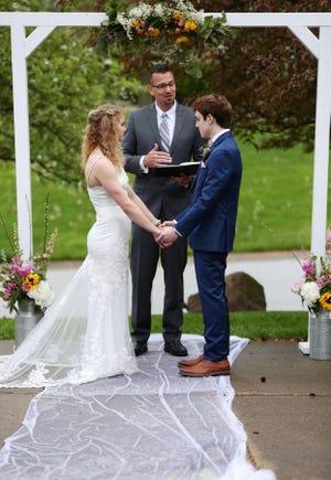 Чейз та Саді Сміт стоять біля весільного вівтаря, встановленого на проїжджій дорозі, де вони поділилися своїм першим поцілунком.