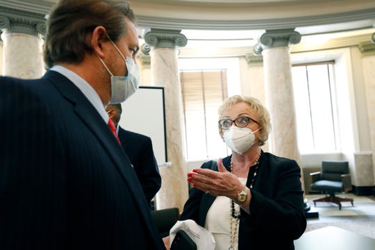 State Superintendent Carey Wright, right, and Sen. Scott DeLano, R-Biloxi, follow virus protocol and remain masked while conferring following a legislative hearing on distance learning and broadband for schools Wednesday, May 13, 2020, at the Capitol in Jackson, Miss. The impact of COVID-19 forced school closure statewide and use of the existing broadband system for learning proved to be taxing, especially in rural communities. (AP Photo/Rogelio V. Solis)