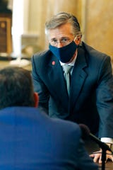 Mississippi AT&T president Mayo Flynt, follows virus protocol by remaining masked while speaking to a lawmaker following a legislative hearing on distance learning and broadband for schools Wednesday, May 13, 2020, at the Capitol in Jackson, Miss. The impact of COVID-19 forced school closure statewide and use of the existing broadband system for learning proved to be taxing, especially in rural communities. (AP Photo/Rogelio V. Solis)