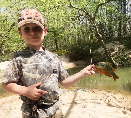 Gunner Johns of Copiah County holds a long-eared sunfish he caught in Copiah Creek.