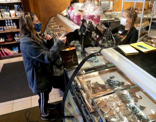 Margo Zimmerman, left, of Mequon, makes a purchase with the help of employee Caleigh Mentzer at Amy's Candy Kitchen in Cedarburg, which is among area businesses that have reopened.