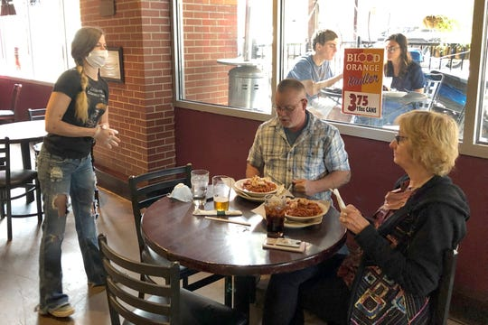Anna Barnard, left, wears a protective mask as she talks to Greg and Judy Robinson at Dugan's Pub in Little Rock on Monday, May 11. Restaurants in Arkansas were allowed to resume offering dine-in service on May 11 after they had been limited to delivery or carryout because of the coronavirus pandemic.