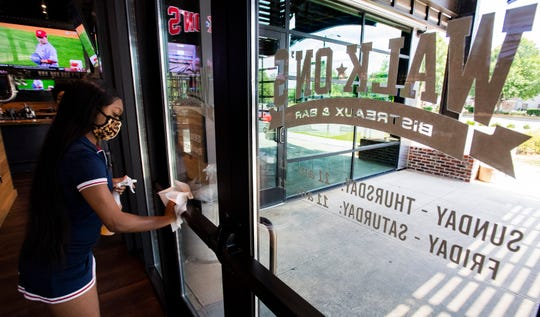 Walk-On's employee Shakia Bailey disinfects doors at the restaurant in EastChase in Montgomery, Ala., on Wednesday May 13, 2020.