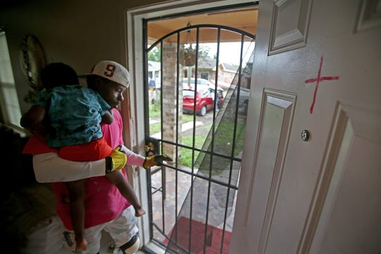 Shawn Dubose holds Ishawn Dubose, 3, next to a cross Nina Shelby-DuBose painted on the door of the home at the beginning of the pandemic to keep anything negative from entering their Ninth Ward home. The family is dealing with securing enough food for their large family with few grocery options in the neighborhood during the COVID-19 pandemic. Photographed on Saturday, May 9, 2020.