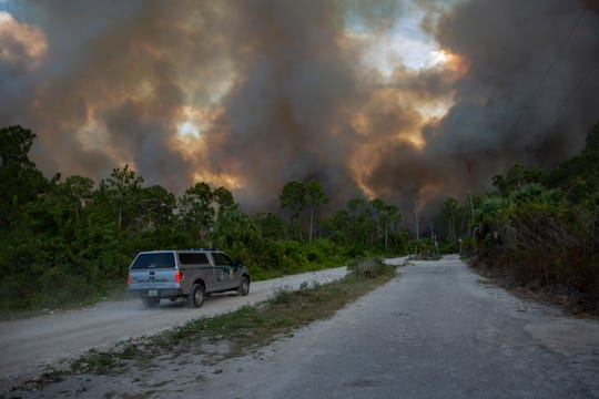 A Florida State Police vehicle drives down Dove Tree Street near the scene of a brush fire on Wednesday, May 13, 2020 in Golden Gate Estates. Crews worked to contain four brush fires totaling about 400 acres and threatening 30 homes in the Estates.