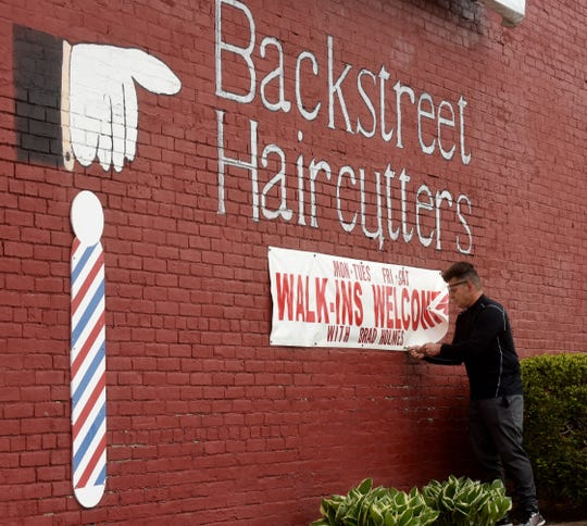 Rob Romine, owner of Backstreet Haircutters in downtown Newark, takes down a sign advertising walk-in appointments on Tuesday, in advance of reopening on Friday. The barber was on a state advisory board about reopening personal care services such as hair salons, barbershops, day spas and nail salons. His shop will offer services by appointment, asks clients to wear masks along with the staff, and has made changes to facilitate distancing.