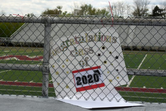 Newark High School graduating seniors drive-through White Field to pick up their caps and gowns as well as instructions for submitting their photos and cap toss for a virtual graduation video on Tuesday, May 12, 2020. Caps and gowns were distributed by representatives from Herff-Jones. Those who could not make Tuesday's pick up can come to the high school's main office beginning on Monday, May 18.