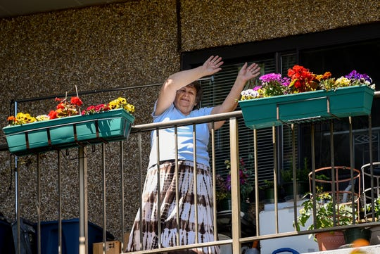 A woman participates in a socially distant exercise class from her balcony at Belmont Gardens in Garfield on Wednesday May 13, 2020.