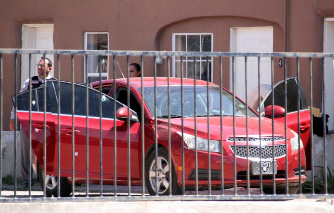 Deming police investigators examine a 2012 Chevrolet Cruz that was struck several times by bullets during a Tuesday morning drive-by shooting at the Coronado Apts., 701 W. Spruce St.