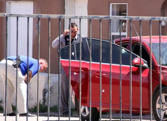Deming police investigators Lee Jordan Cook (left) and James Fetrow examine bullet holes in the passenger-side door of a 2012 Chevrolet Cruz.