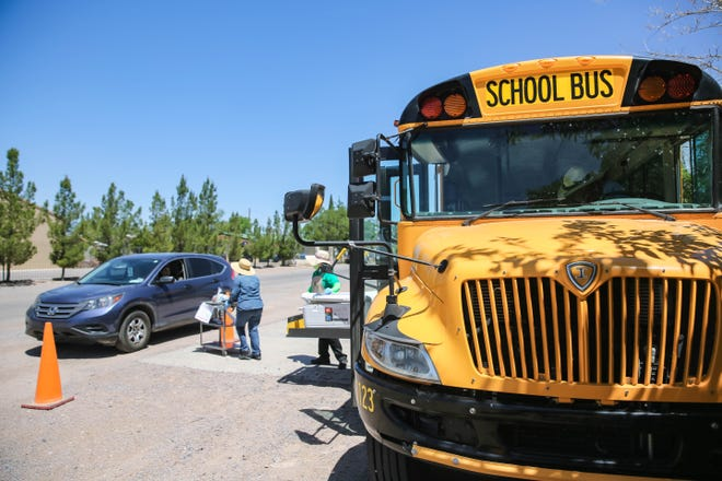 A school bus serves as a mobile hotspot for students to use for homework in the rural community of Berino, N.M. on Wednesday, May 13, 2020. New Mexico schools have shifted to remote learning for the remainder of the school year because of the COVID-19 pandemic.