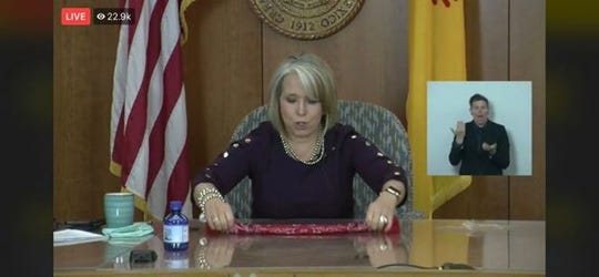 New Mexico Gov. Michelle Lujan Grisham demonstrates how to fold a homemade face mask during a virtual news conference from the state Capitol building in Santa Fe on Wednesday, May 13, 2020.
