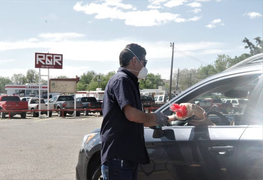 Marco Serna hands a loaf of bread to someone who visited his food, glove and mask distribution, Tuesday, May 12, 2020, in Farmington.