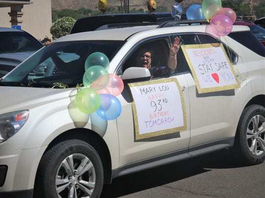 A participant in the Parking Lot Love Parade waves to residents of The Bridge at Farmington assisted living on May 13, 2020.