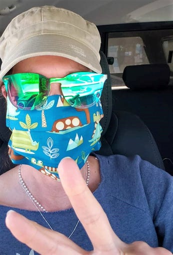 """Pamela Witte shows off her mask made by """"Project Facemask."""" Designs vary and are colorful. The project began production in the wake of COVID-19 when a need for PPEs became more apparent since April, 2020."""