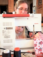 """Kirby Ann Witte Taggart teaches her daughter how to sew masks for """"Project Facemask."""" The project has made hundreds of masks since the pandemic began in March 2020."""