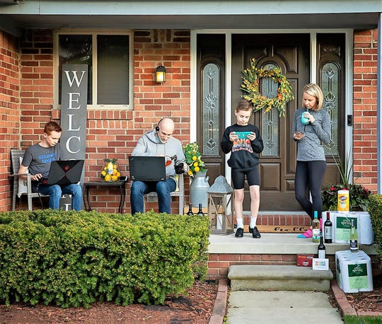 Tracy Murley (right), the orchestrator of the Plymouth/Canton Sisterhood of the Traveling Wine, is pictured with her family on their Canton porch.