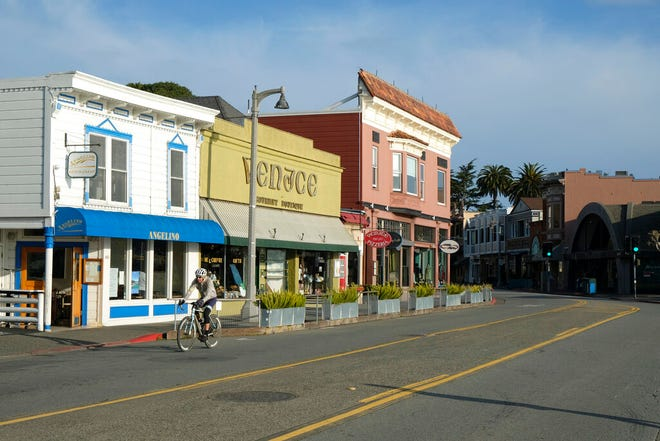 FILE - In this March 17, 2020 file photo a bicyclist rides past closed restaurants and shops in Sausalito, Calif.