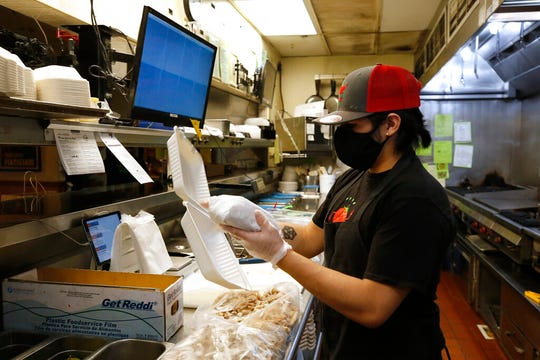 Matthew Sargosa places a sandwich in a takeout container at Dancing Tomato Caffe in Yuba City, Calif., Tuesday, May 12, 2020.