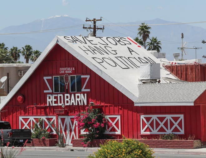 "A message that reads ""Save Jobs!  Hang a Politician"" has been painted in a prominent position on the Red Barn bar's roof in Palm Desert, May 13, 2020."