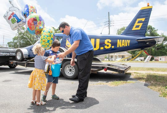 Birthday boy Jacob Durden, 7, gets help opening a present from his sister Aspen, 4, and father Mike Durden as they stand in front of Gerry and Karen Moore's new Blue Angels car at Compu-Graphix in Pensacola on Wednesday. Family and friends gathered there to celebrate Jacob's seventh birthday.
