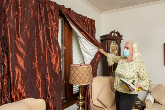 Margaret Hostetter shows the heavy curtains and blinds that cover the windows in one of her short-term East Hill rental properties in Pensacola on Wednesday.