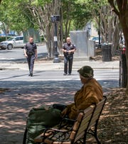 Pensacola Police Department Capt. Stephen Davis, left, and Chief Tommi Lyter walk through Martin Luther King Jr. Plaza along Palafox Street in downtown Pensacola on Tuesday, May 11, 2020.  The number of homeless and vagrants in downtown has increased during the coronavirus shutdown.