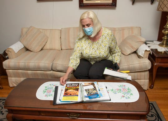 Margaret Hostetter shows the information and guestbook in one of here short-term East Hill rental properties on Wednesday.