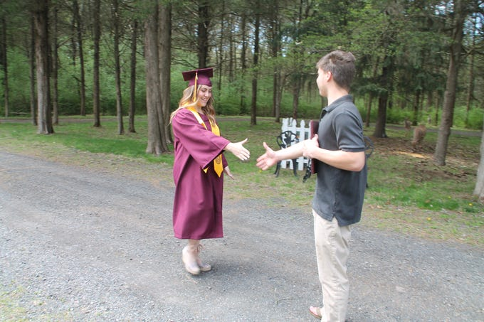 Gabrielle Bancroft receives a diploma from her brother during an impromptu graduation ceremony in her parents' driveway to celebrate her Arizona State University degree.
