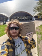 Tyler Day dressed in Northern Arizona University colors and created a stand-in diploma to celebrate his graduation.