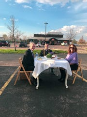 Vince Clapper and his parents set up a dinner table in the Texas Roadhouse parking lot in Sioux Falls, South Dakota, to celebrate his graduation from Grand Canyon University.