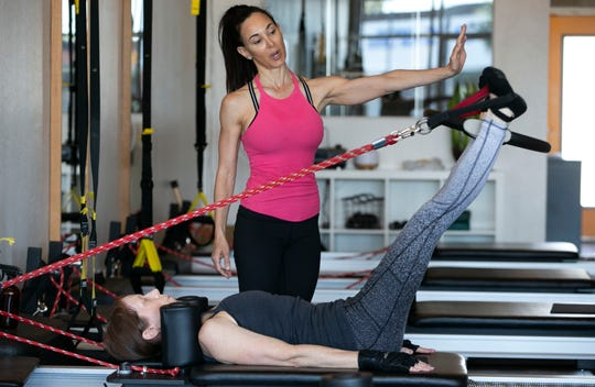 Pilates instructor Elizabeth Valasek, top, leads a one-on-one session with Elizabeth Feldman of Phoenix, at Verve Pilates and Wellness in Phoenix on May 13, 2020, on the first day that gyms were allowed to reopen in Arizona since mid-March because of the COVID-19 pandemic.