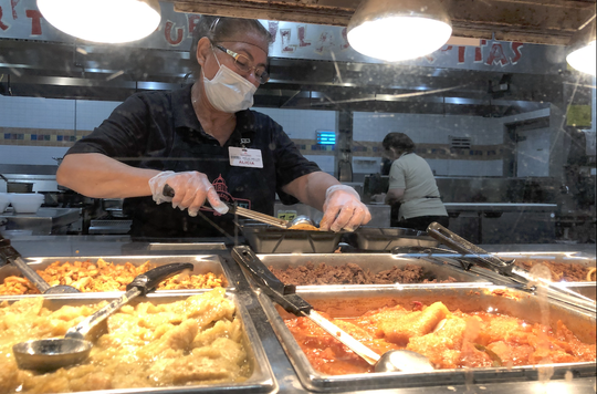 With face mask and gloves, cook at Los Altos Ranch Market prepares a dish.