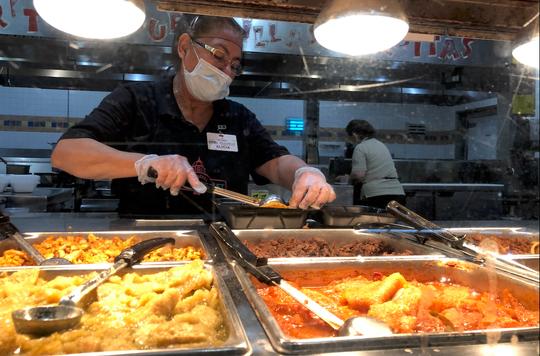 Con cubre bocas y guantes, cocinera de Los Altos Ranch Market prepara un platillo, el 12 de mayo de 2020.