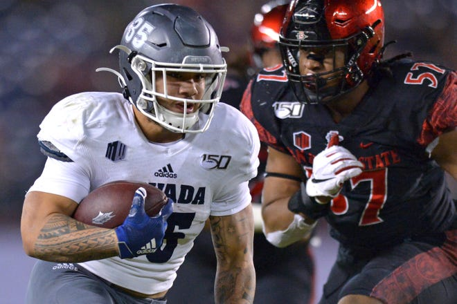 Nevada's Toa Taua (35) runs past San Diego State defensive lineman Keshawn Banks during the Wolf Pack's win in San Diego last season.