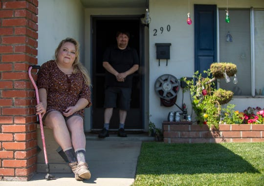 Lori Long is photographed sitting on a bench in front of her Salinas home as her fiancé Mark Contreras stands in the background on Thursday, April 30, 2020.