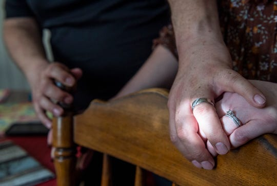 Lori Long and her fiancé Mark Contreras, hold hands as the sunlight coming through a window hits their engagement rings on Thursday, April 30, 2020.