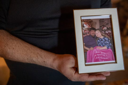 Mark Contreras, left, holds a framed photo of him and his fiancée Lori Long, on Thursday, April 30, 2020. The couple is covered in a pink blanket that Contreras designed when he proposed to Long.