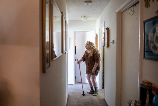 Lori Long, looks at old photos of her fiancé Mark Contreras in the hallway of their Salinas home on Thursday, April 30, 2020.