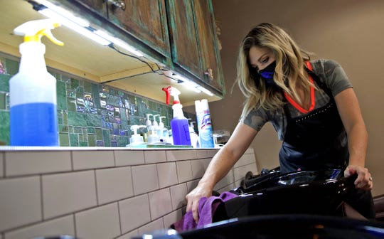 Tori Stubbs, owner of the Burlap and Paisley Boutique and Salon, sanitizes a hair washing station Friday, May 8, 2020 after hair salons were allowed to reopen for business in Texas.