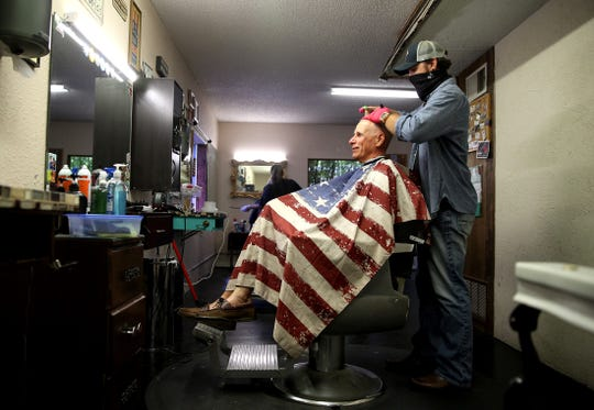 Bill Procter, seated, gets his hair cut by Preston Shaver at the Vintage Barber on Tuesday, May 12, 2020 after Texas allowed barbershops and hair salons to reopen.