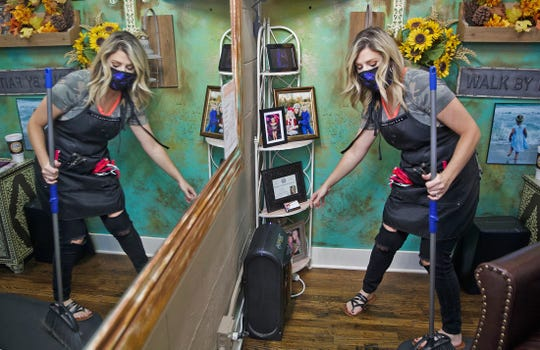 Tori Stubbs, owner of the Burlap and Paisley Boutique and Salon, sanitizes a booth Friday, May 8, 2020 after hair salons were allowed to reopen for business in Texas.