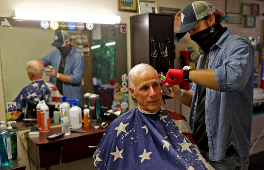 Bill Procter, center, gets his hair cut by Preston Shaver, right, at the Vintage Barber on Tuesday, May 12, 2020 after Texas allowed barbershops and hair salons to reopen.