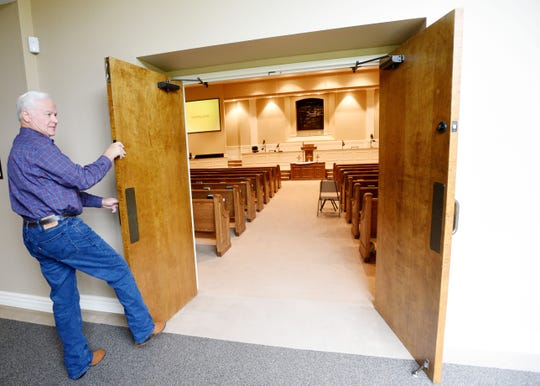 Ellerbe Baptist Church's Pastor Dennis Sims shows how the doors will remain open when they continue service.