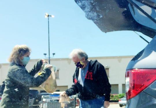 People load groceries in their car in Shreveport during the coronavirus.