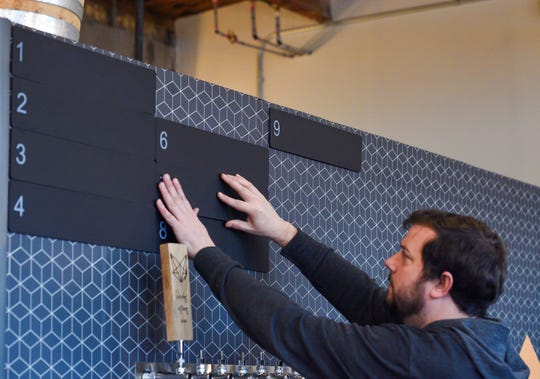 Daniel Berry hangs erasable menu boards in Covert Cellars on Wednesday, May 13, on 8th Street in Sioux Falls.