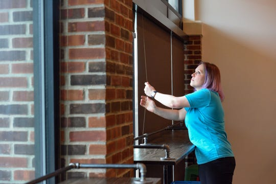Stacey Berry opens the blinds to let sunlight into in the new Covert Cellars location on Wednesday, May 13, on 8th Street in Sioux Falls.