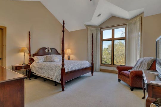 Double entry doors and vaulted ceilings provide the master bedroom with a dramatic flair and a bay window lets in the natural light.