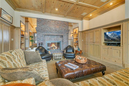 Opposite the foyer, on the other side of the fireplace, is the great room with built-ins that house an entertainment center and fantastic bay windows with views of the outdoors.