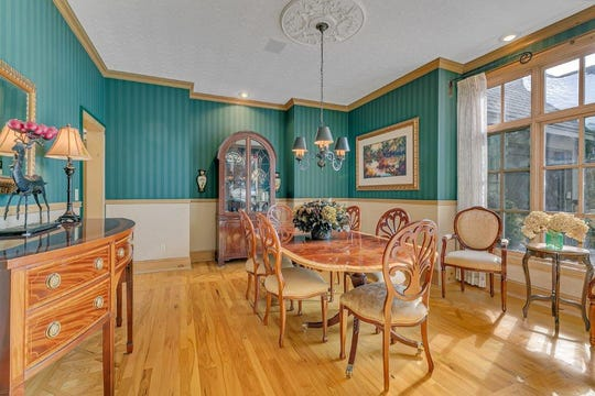 The formal dining room features 10-foot ceilings as well as hickory hardwood flooring with parquet accents.